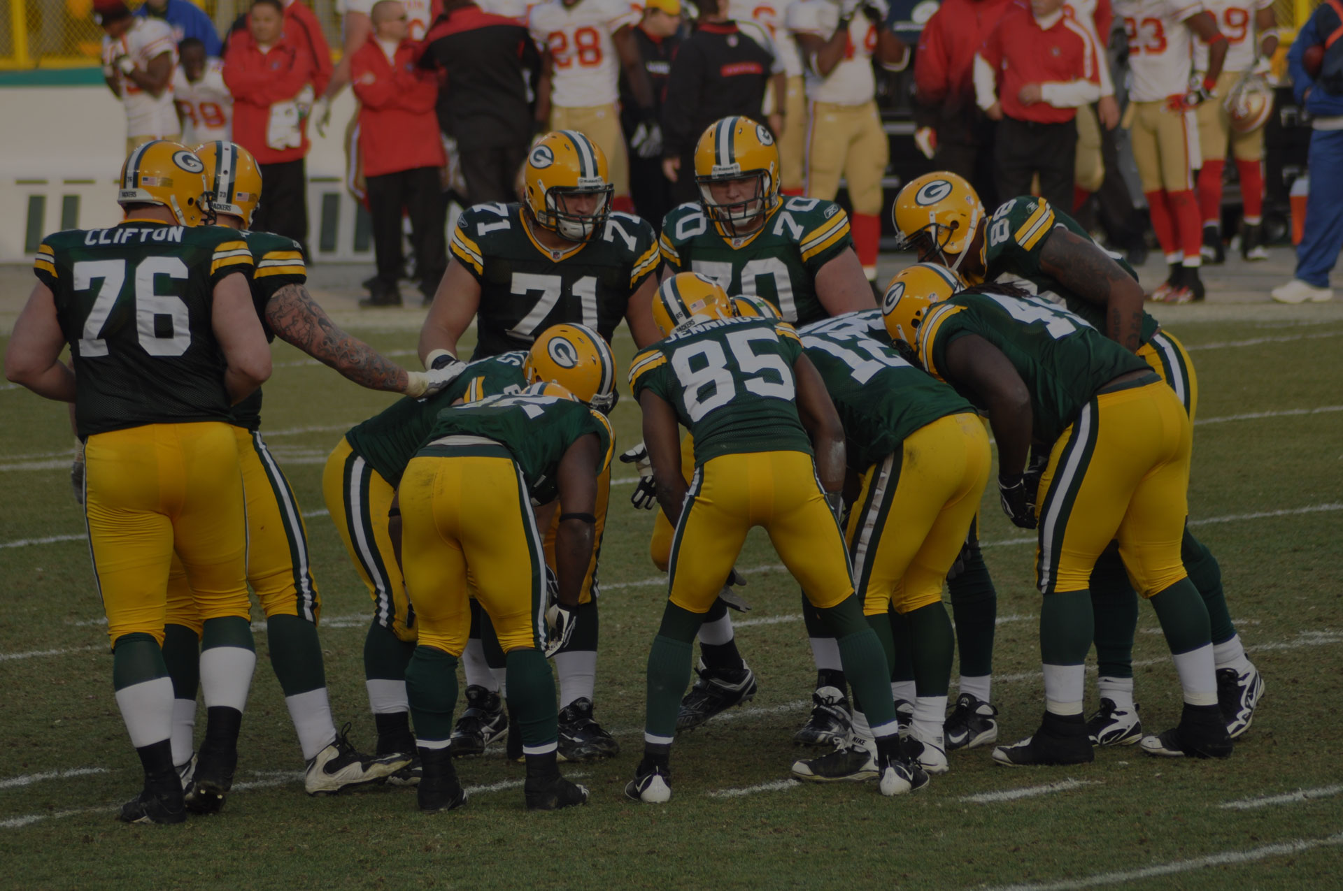 Green Bay Packers offense with quarterback Aaron Rodgers huddles in a game at Lambeau