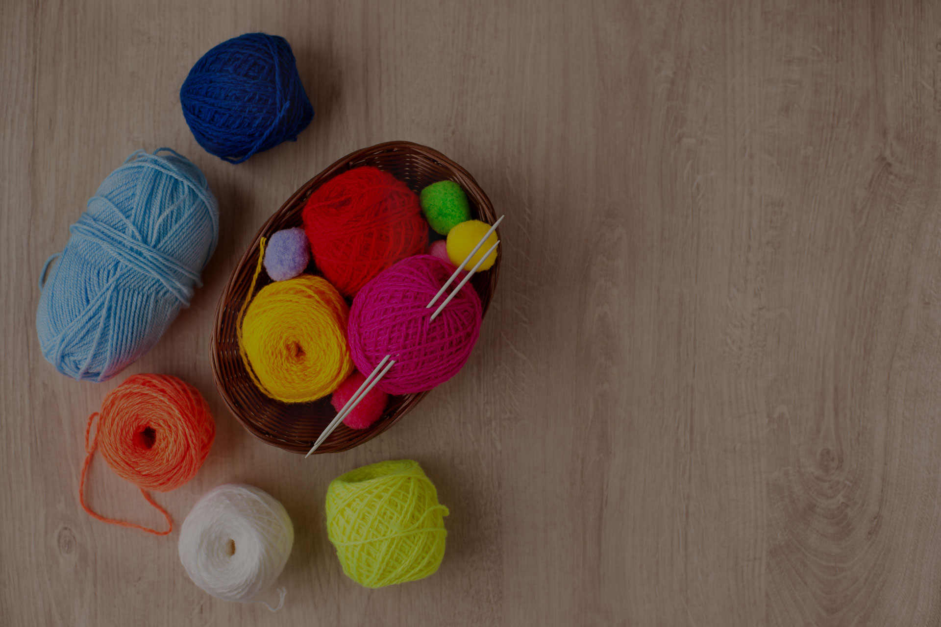 Knitting needles and multi-colored yarn look bright.